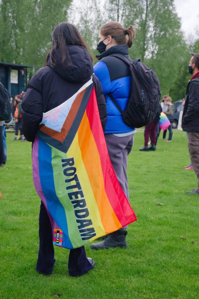 """Iemand met om hun lijf een regenboogvlag met de tekst """"Rotterdam"""" erop."""