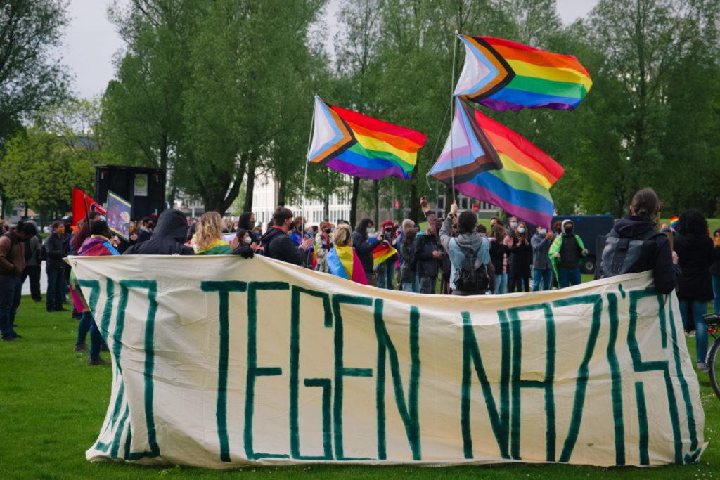 """Groot spandoek """"010 tegen nazi's!"""". Op de achtergrond veel regenboogvlaggen."""