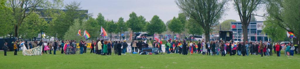 Breedbeeldfoto met een overzicht van de demo. Veel regenboogvlaggen.