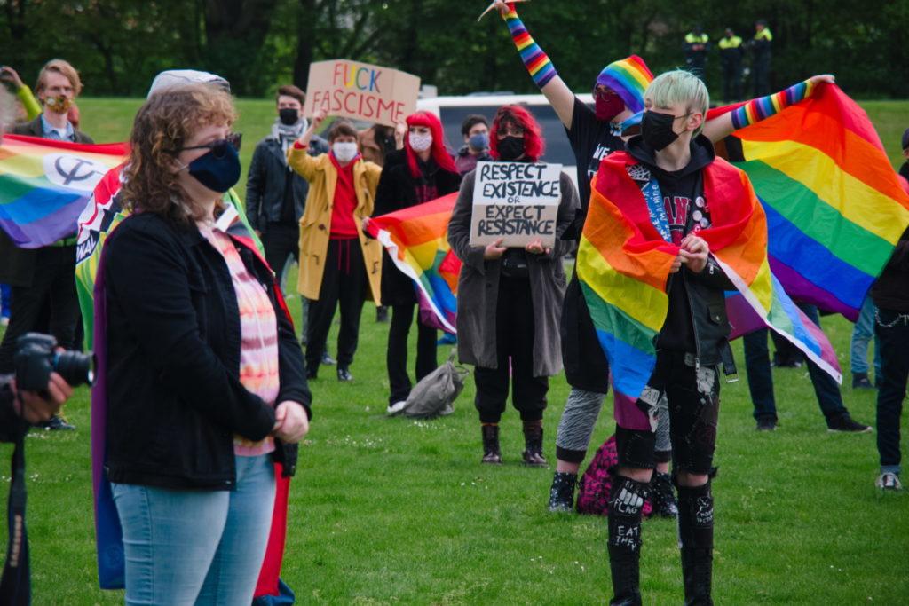 Op de achtergrond een activist met lange regenboog-armwarmers. Op de voorgrond iemand met de regenboogvlag om het lijf geslagen als een soort omslagdoek.