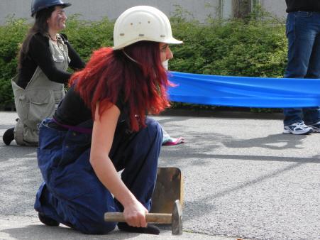 Optreden van vrouwengroep Street Amazons over hoe van alle kanten aan vrouwen getrokken wordt. Hier: werken in de fabriek.