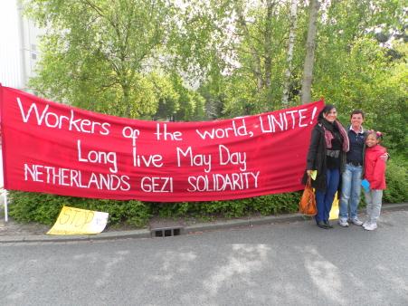 Spandoek van de groep Gezi Solidariteit Nederland, met twee solidaire SP-raadsleden er naast.