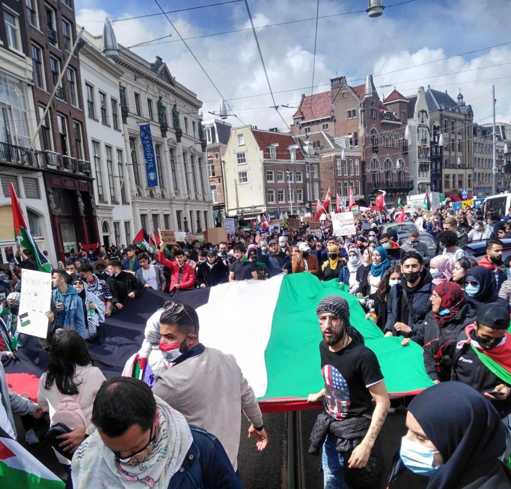 Demonstranten dragen een enorme Palestijnse vlag mee in Amsterdam.