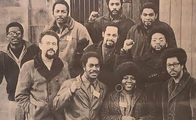 Groepsfoto van allemaal zwarte strijders, een deel met geheven vuisten.
