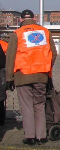 Actievoerder bij de poort, in FNV-hesje met logo van het comité erop.