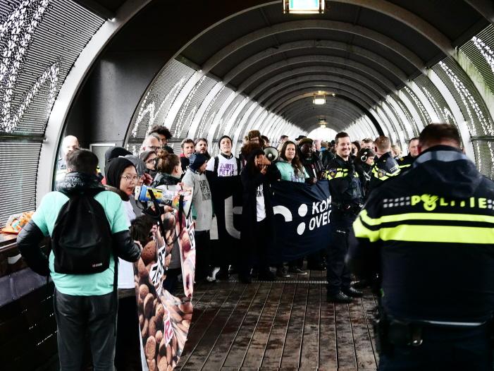 Beide groepen actievoerders bijeen op de loopbrug nadat de politie rechts een doorgang had gemaakt (foto: Jeroen van Wisse)
