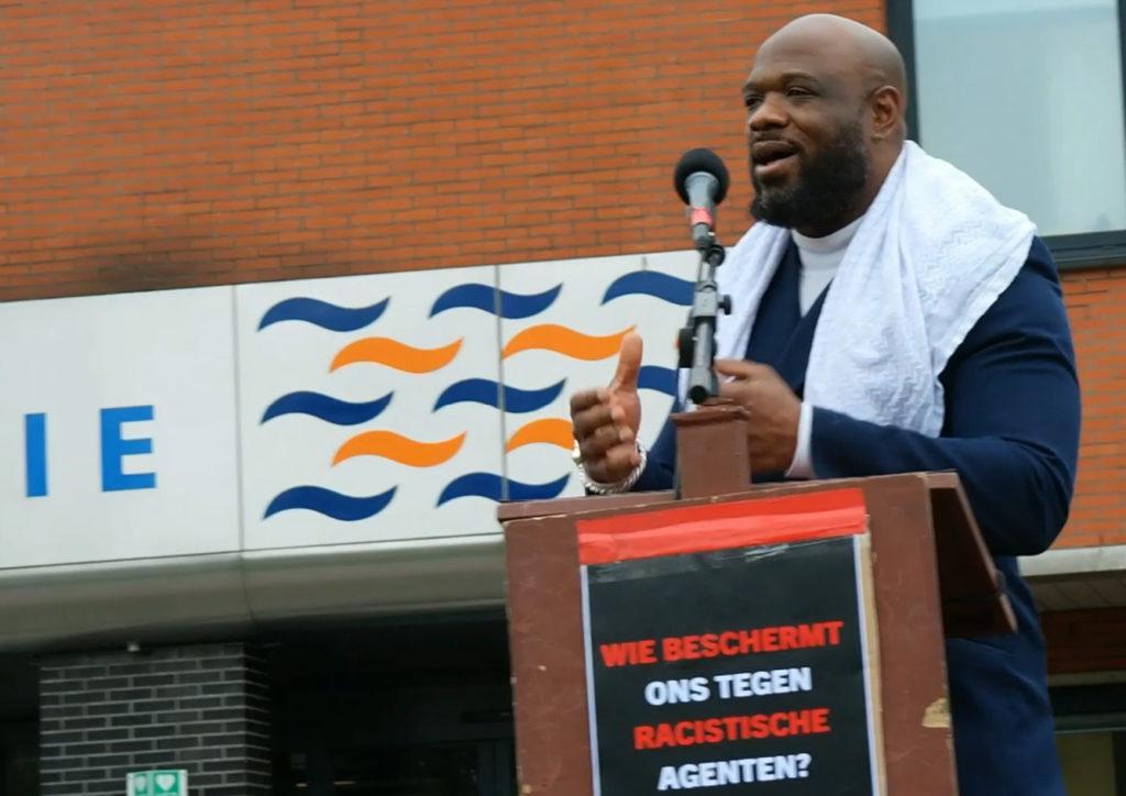 Elvin Rigters achter de microfoon. Hij heeft een witte sjaal om zijn schouders en een donkerblauw jasje aan.