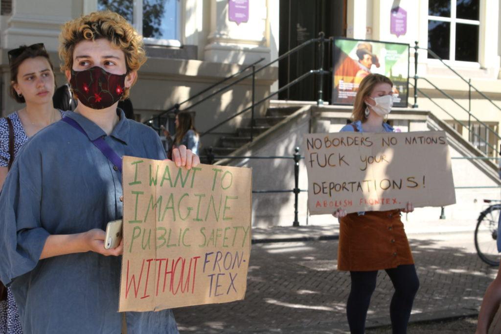 Twee demonstranten met hun borden. Ze staan voor het Mauritshuis.