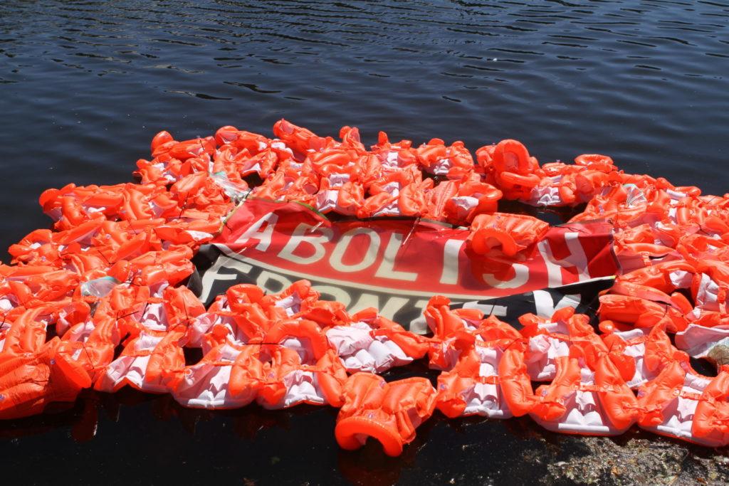 """Een heleboel zwemvesten in de Hofvijver die een spandoek laten drijven met daarop de tekst """"ABOLISH FRONTEX""""."""