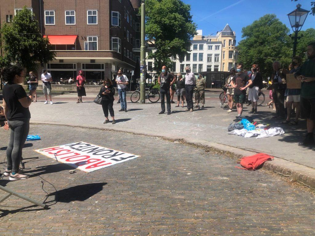 """Een spreker staat achter een op de grond liggend spandoek met de tekst """"Abolish Frontex""""."""