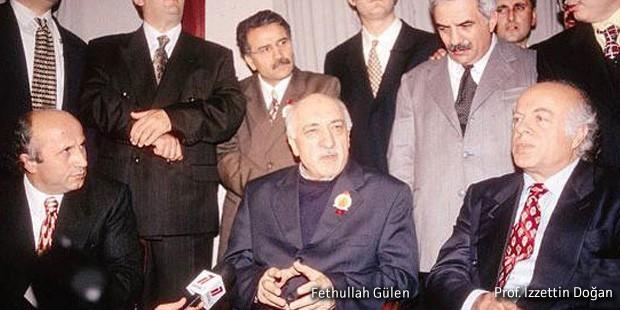 Foto met op de voorgrond Fethullah Gülen in een donkerblauw pak met een insigne op het revers, naast hem Prof. Izzettin Doğan in een donkerblauw pak en een rode stropdas. Op de achtergrond nog veel meer mannen in ouderwetse 'nette' pakken.