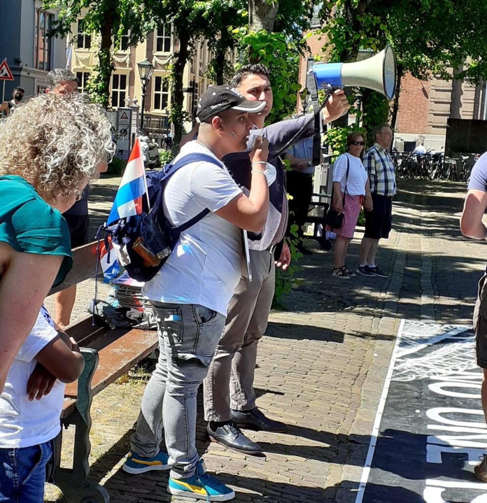 Een demonstrant met een rugzak op met een Nederlands vlaggetje eraan spreekt in de megafoon, die door iemand anders wordt vastgehouden.