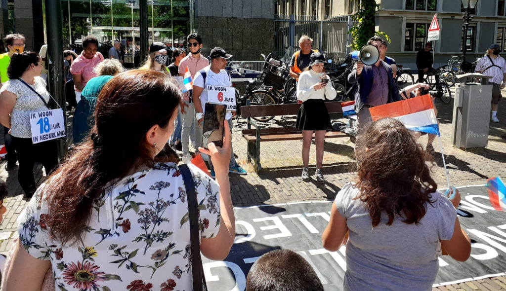 Een jonge demonstrant voert het woord en leest iets op van een smartphone. Omstanders dragen borden waarop te lezen is hoe lang ze al in Nederland zijn.
