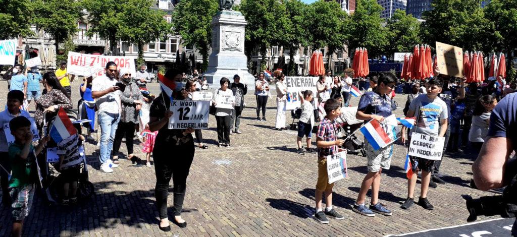 De demonstranten rondom een beeld op het plein. Op de achtergrond terrassen.