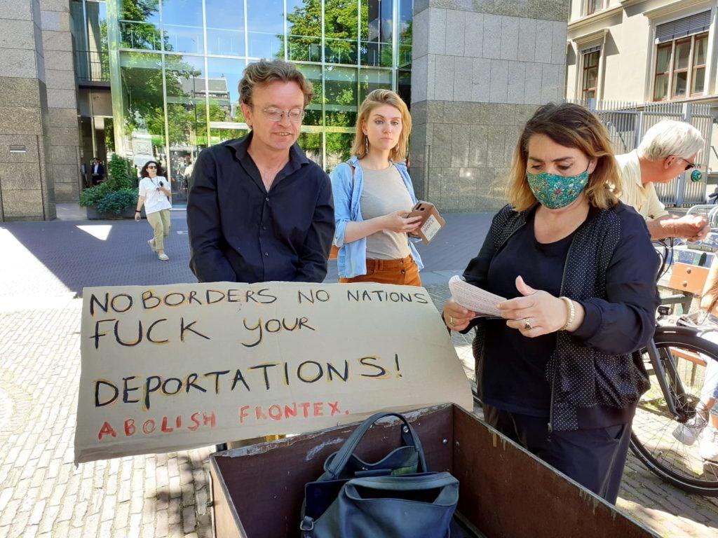 """Fatima Faïd met een groen mondkapje met bloemen erop naast een bakfiets waarop een bord ligt met de tekst """"No borders no nations, fuck your deportations! Abolish Frontex."""""""