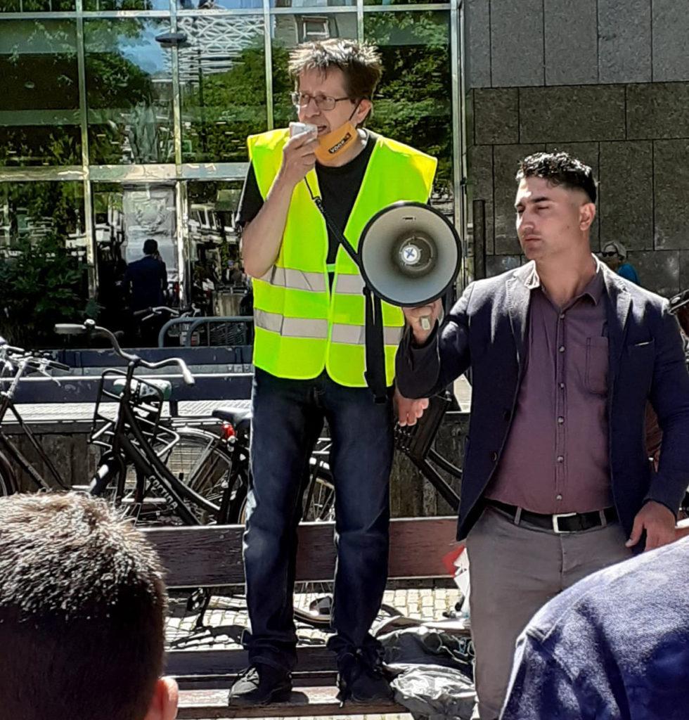 Eén van de sprekers voert het woord terwijl iemand naast hem de megafoon vasthoudt.