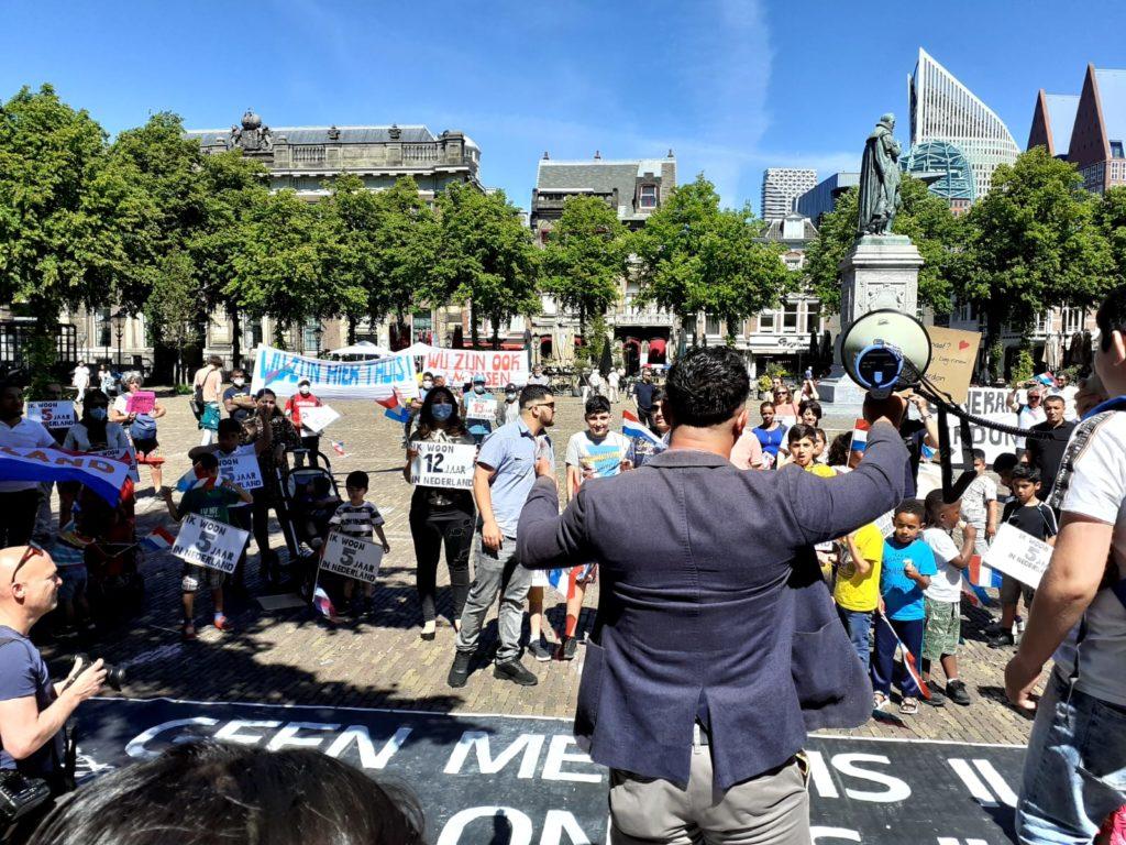 We kijken op de rug van één van de sprekers richting de demonstranten.