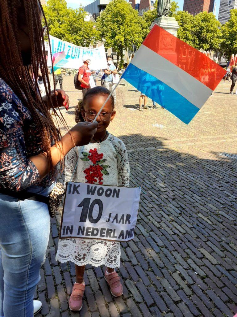 """Een kind met een mooie bebloemde kanten jurk aan draagt een bord """"Ik woon 10 jaar in Nederland"""". Naast het kind staat iemand met veel vlechtjes in het haar en een Nederlands vlaggetje in de hand."""