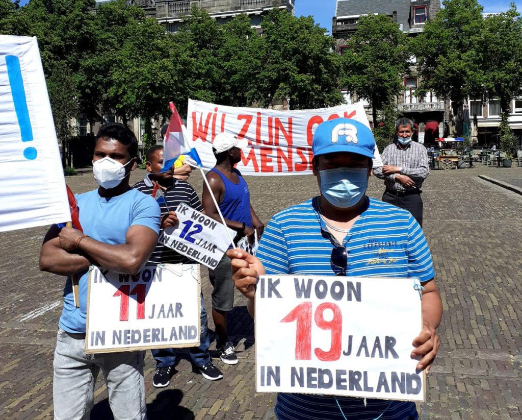 Twee demonstranten met hun mondkapjes op en borden die zeggen hoe lang ze in Nederland zijn (11 en 19 jaar).