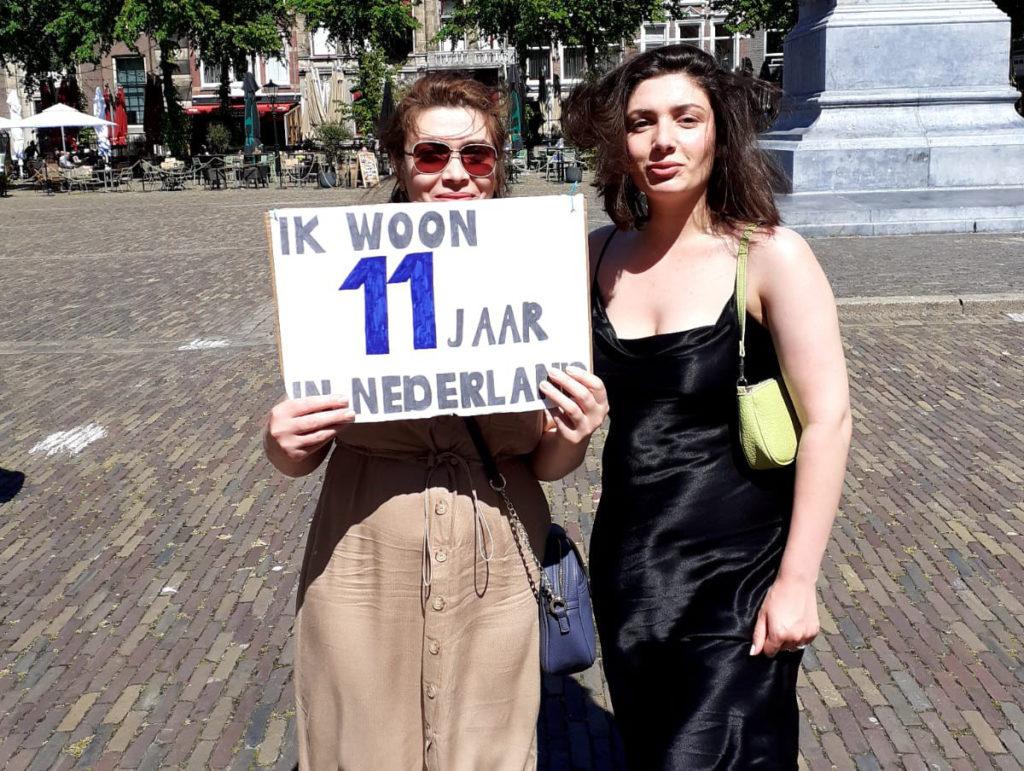 """Twee mensen waarvan eentje in een zwarte satijnen jurk en de ander een bruine rok, deze draagt een bord """"Ik woon 11 jaar in Nederland""""."""