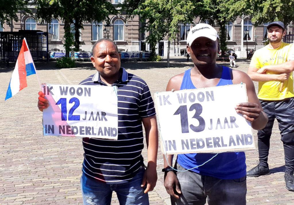 Twee mensen waarvan eentje in een blauw streepjesshirt en de andere in een blauw hemd met borden dat ze 12 en 13 jaar in Nederland zijn.