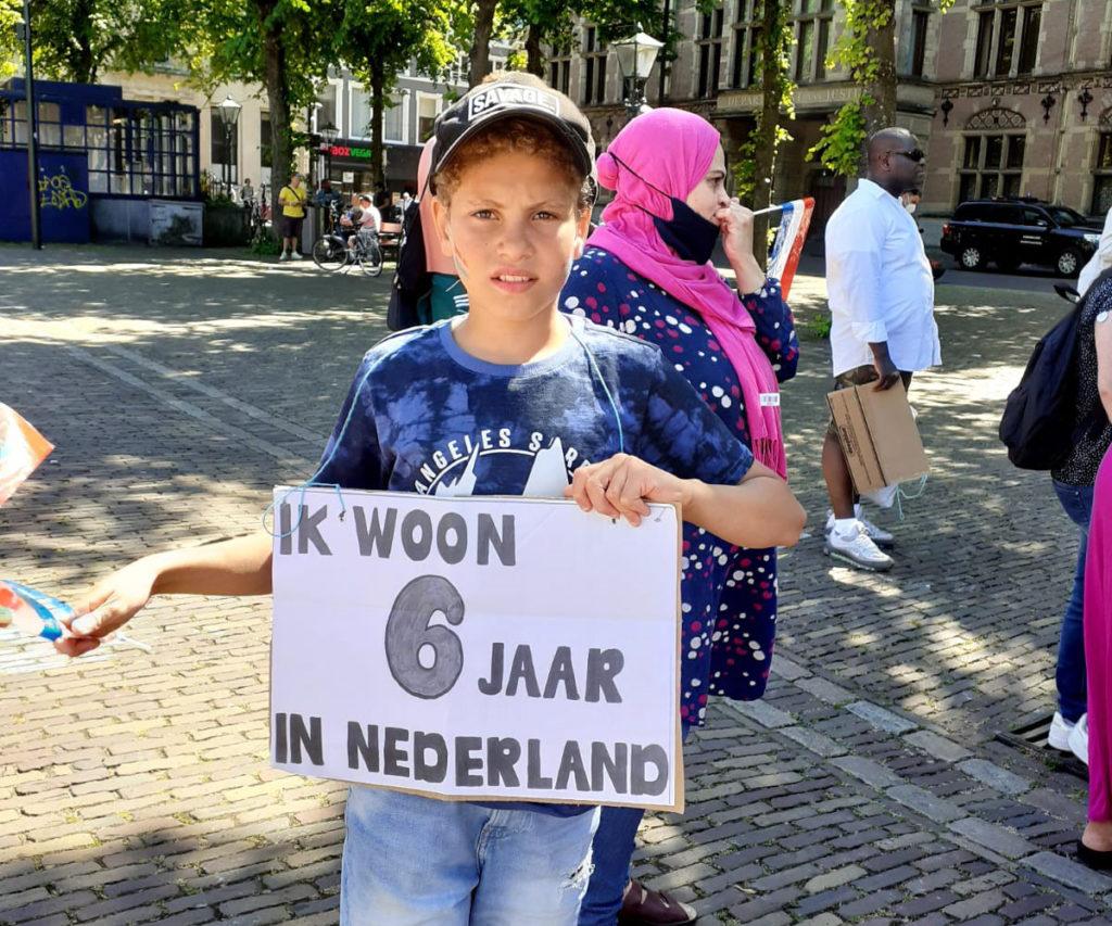 """Een kind met een zwart petje op draagt een bord met de tekst """"Ik woon 6 jaar in Nederland""""."""