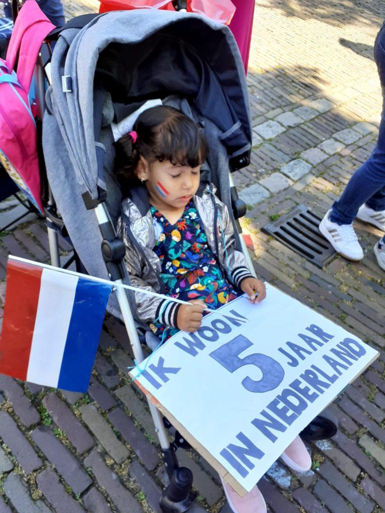 """Een kindje is in slaap gevallen in de buggy , met een Nederlands vlaggetje in de hand en een bord op schoot met de tekst """"Ik woon 5 jaar in Nederland""""."""