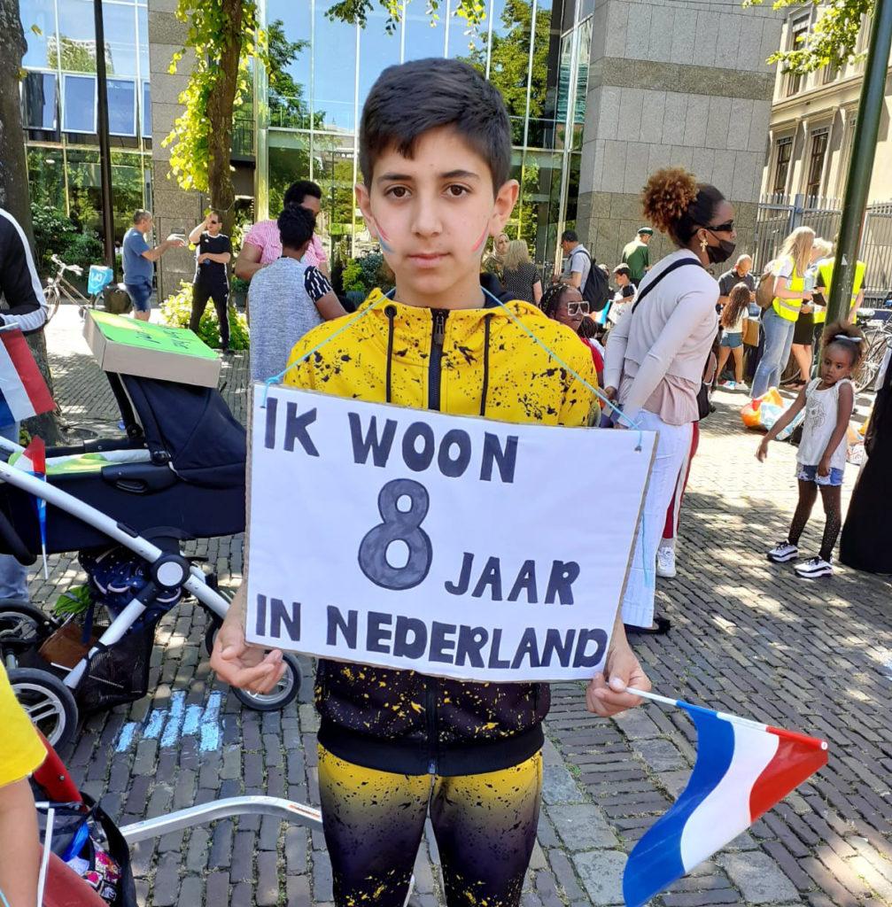 """Een kind met een fel geelzwart trainingspak aan en Nederlandse vlaggetjes op de wangen. Op zijn bord staat """"Ik woon 8 jaar in Nederland""""."""