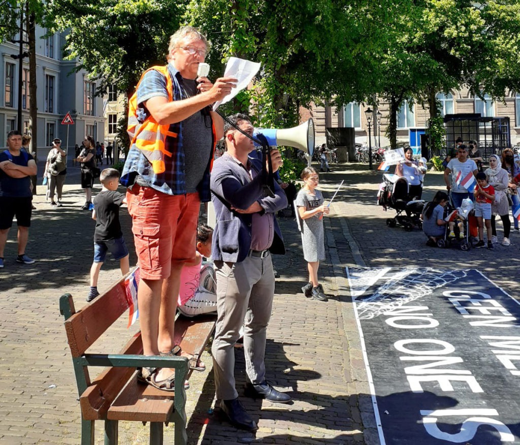 Een spreker voert het woord vanaf een bankje.