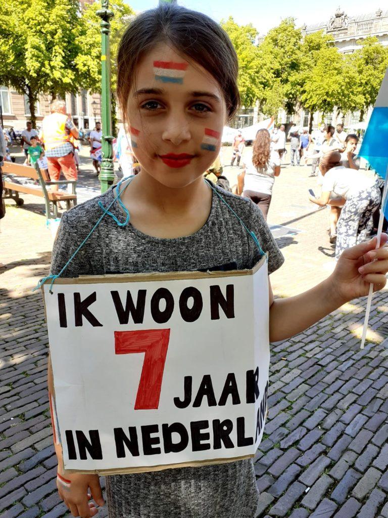"""Een kind dat vriendelijk in de kamer kijkt. Ze heeft drie Nederlandse vlaggetjes op haar gezicht geschminkt staan. Ze draagt een bordje met """"Ik woon 7 jaar in Nederland""""."""