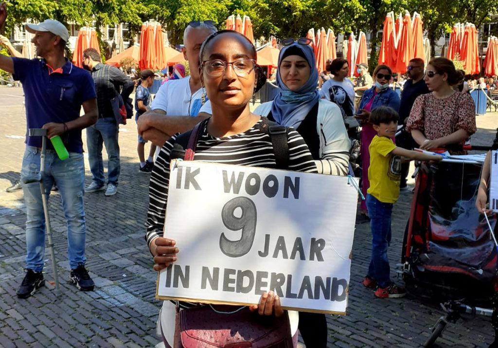 """Iemand met een zwartwit streepjesshirt en een rode tas met een bord """"Ik woon 9 jaar in Nederland""""."""