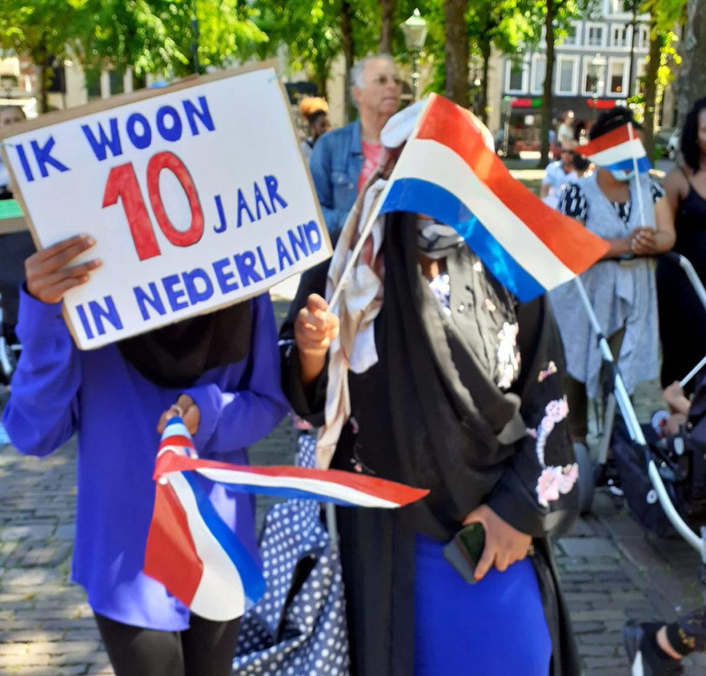 """Twee mensen van wie de gezichten wegvallen achter hun vlaggetjes en een bord met """"Ik ben 10 jaar in Nederland""""."""