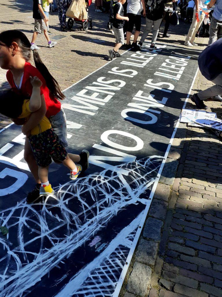 """Heel groot spandoek op de grond met de tekst """"GEEN MENS IS ILLEGAAL / NO ONE IS ILLEGAL"""" met erbij een tekening van een hek met prikkeldraad erboven."""
