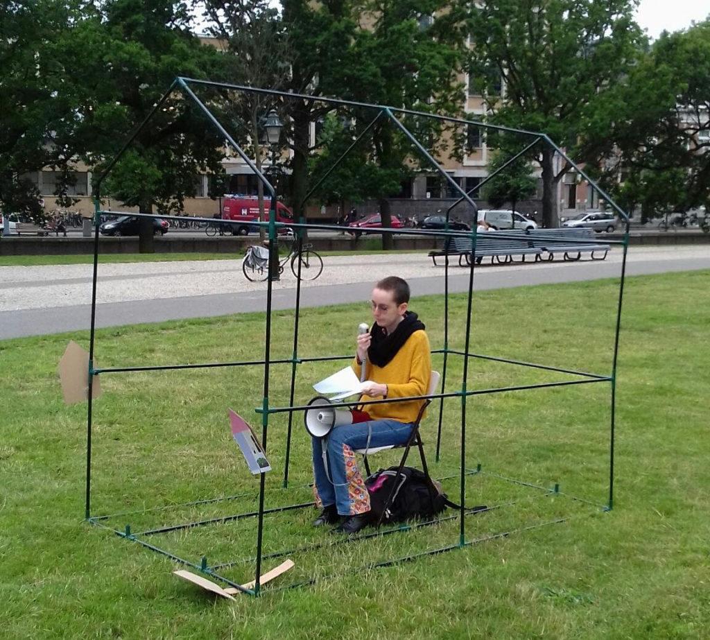 Een activist leest een tekst voor terwijl die in een buizenframe in de vorm van een huis op een stoeltje zit.