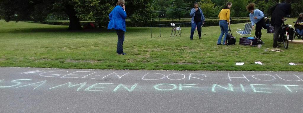 """Op de voorgrond asfalt met daarop een gekrijte tekst: """"Geen dor hout - Samen of niet"""". Op de achtergrond een aantal activisten in het gras."""