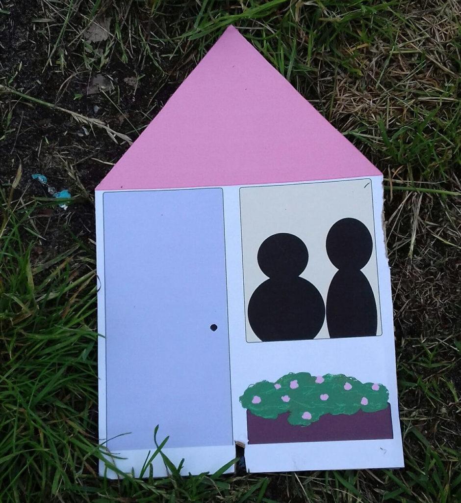 Hetzelfde huisvormige bordje als eerder, maar nu zitten er twee mensen achter het raam.