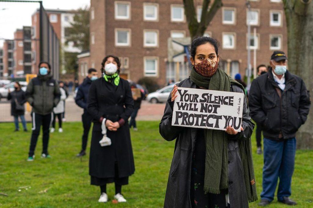 """Een persoon met zwarte haren, een donkere jas en een donkerrood mondkapje draagt een bordje met de tekst """"Your silence will not protect you""""."""