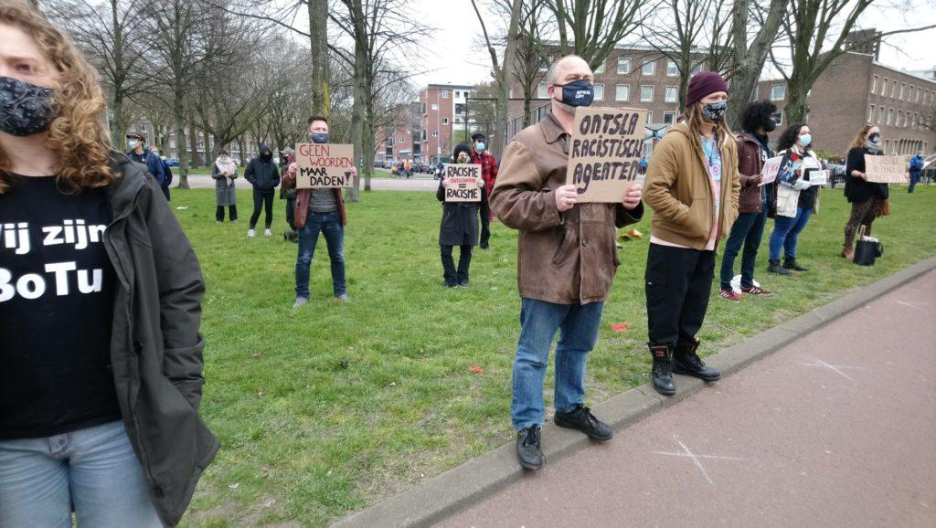 """Een persoon met een bruine leren jas en een spijkerbroek draagt een bordje met de tekst """"Ontsla racistische agenten"""". Om de persoon heen staan op een afstandje nog andere mensen met bordjes, waaronder """"Geen woorden maar daden!"""" en """"Racisme ontkennen = racisme""""."""