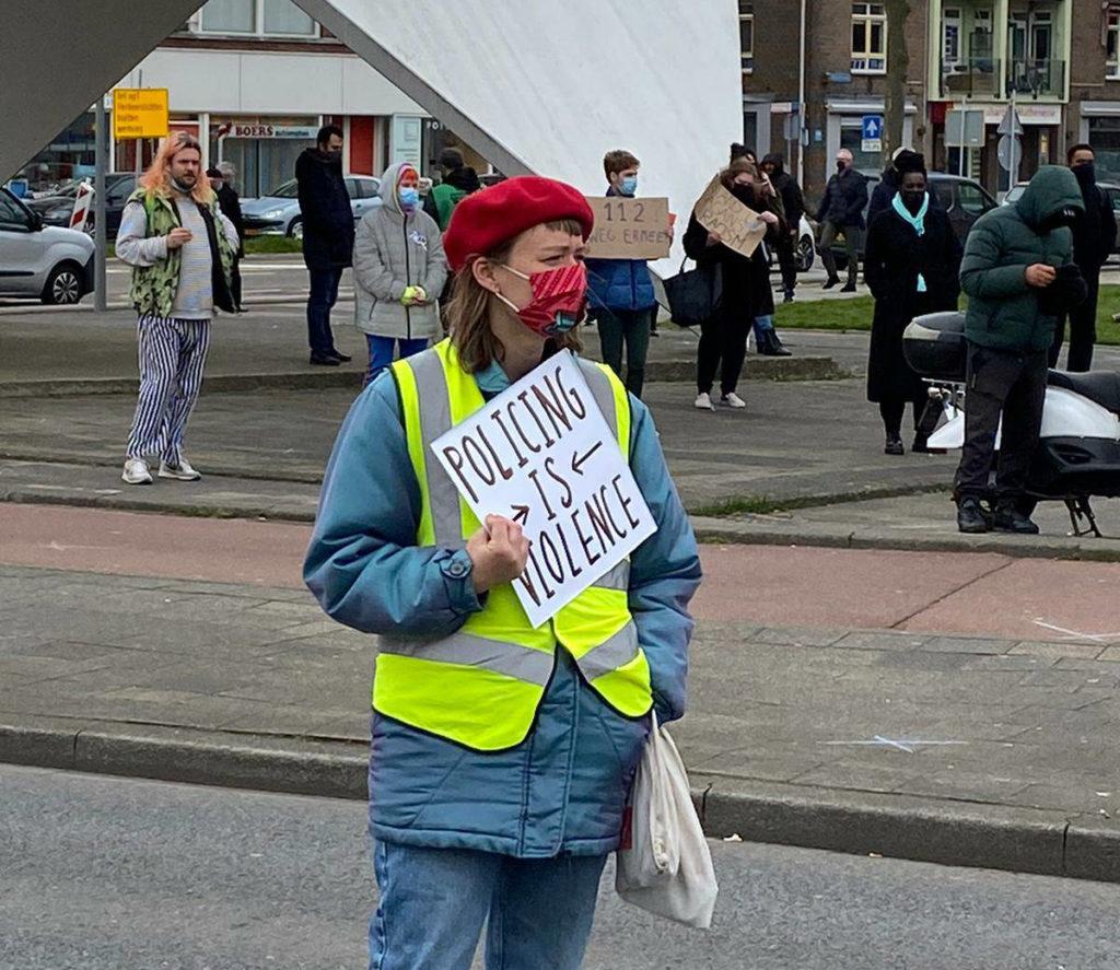 """Een demonstrant met een rode baret en een veiligheidshesje draagt een bordje met de tekst """"Policing is violence""""."""