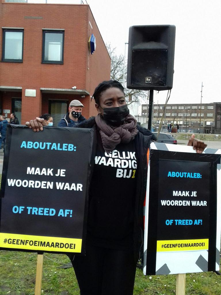 """Een demonstrant met een trui van de politieke partij BIJ1 draagt twee borden met beide dezelfde tekst: """"Aboutaleb: maak je woorden waar of treed af!"""""""