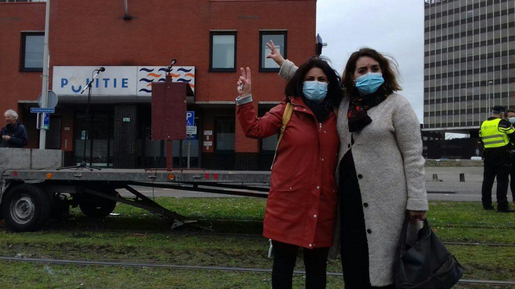 Fatima Faid op de foto met een andere aanwezige op het protest. Ze dragen beide een blauw wegwerpmondkapje en ze maken met hun vingers het vredesteken. Op de achtergrond het politiebureau Marconiplein.