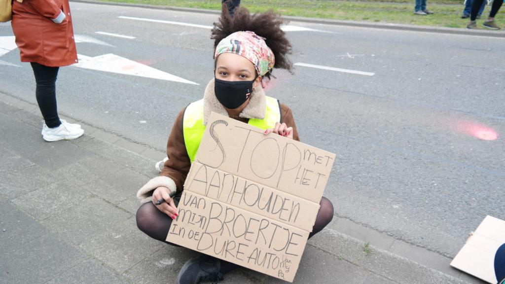 """Een demonstrant met een kleurige doek in het haar en een zwart mondkapje zit in kleermakerszit op de stoep met een bord: """"Stop met het aanhouden van mijn broertje in de dure auto van mijn pa""""."""