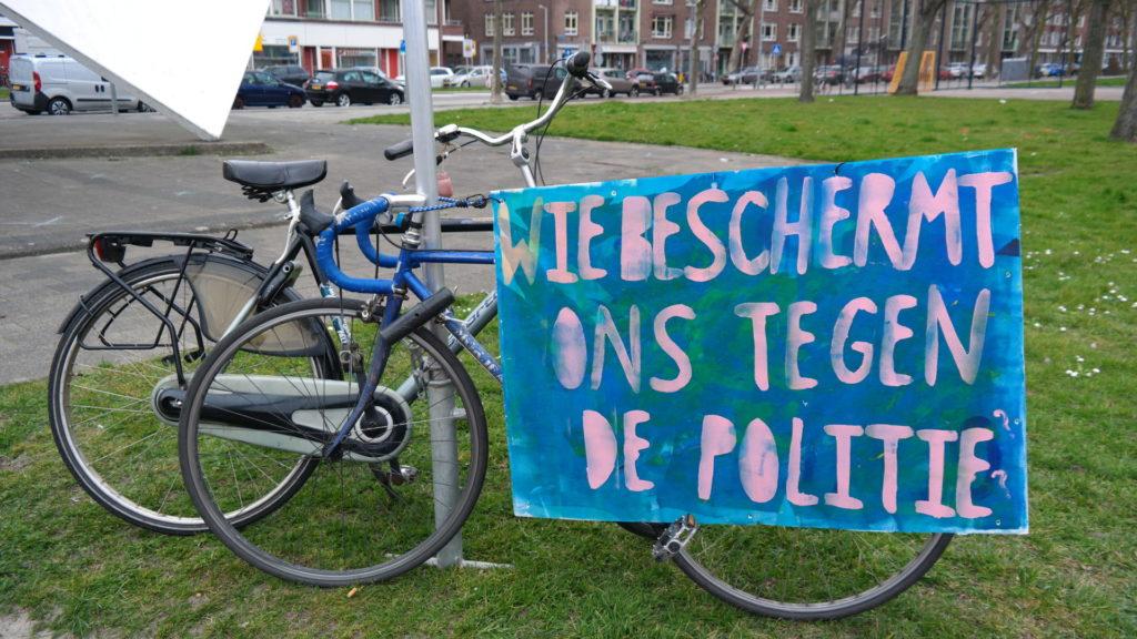 """Twee fietsen tegen een paal en een groot blauw bord met de tekst """"Wie beschermt ons tegen de politie?""""."""