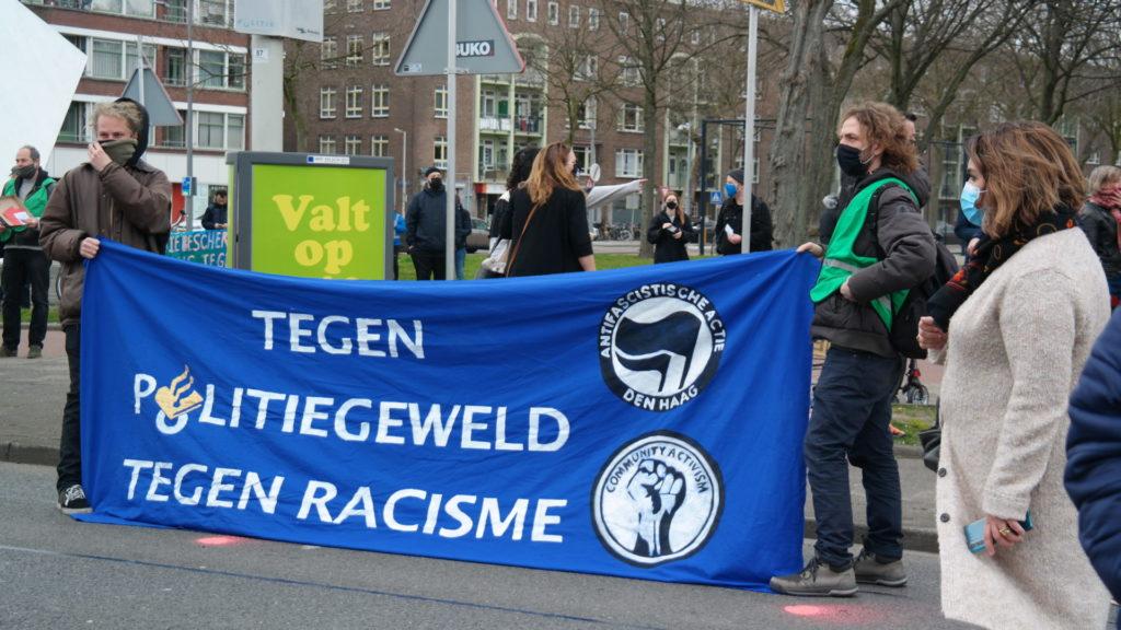 """Groot blauw spandoek met AFA Den Haag logo en de tekst """"Tegen politiegeweld - tegen racisme"""". In de letter o van 'politiegeweld' zit het logo van de politie verwerkt."""