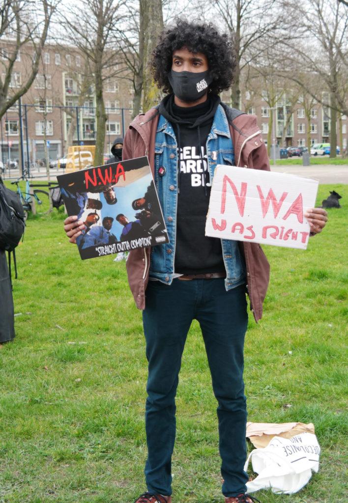 """Daryll Landbrug met de elpee """"Straight outta Compton"""" van N.W.A. en een bordje met de tekst """"NWA was right"""". Daryll draagt een zwart mondkapje met de tekst """"Black Lives Matter""""."""