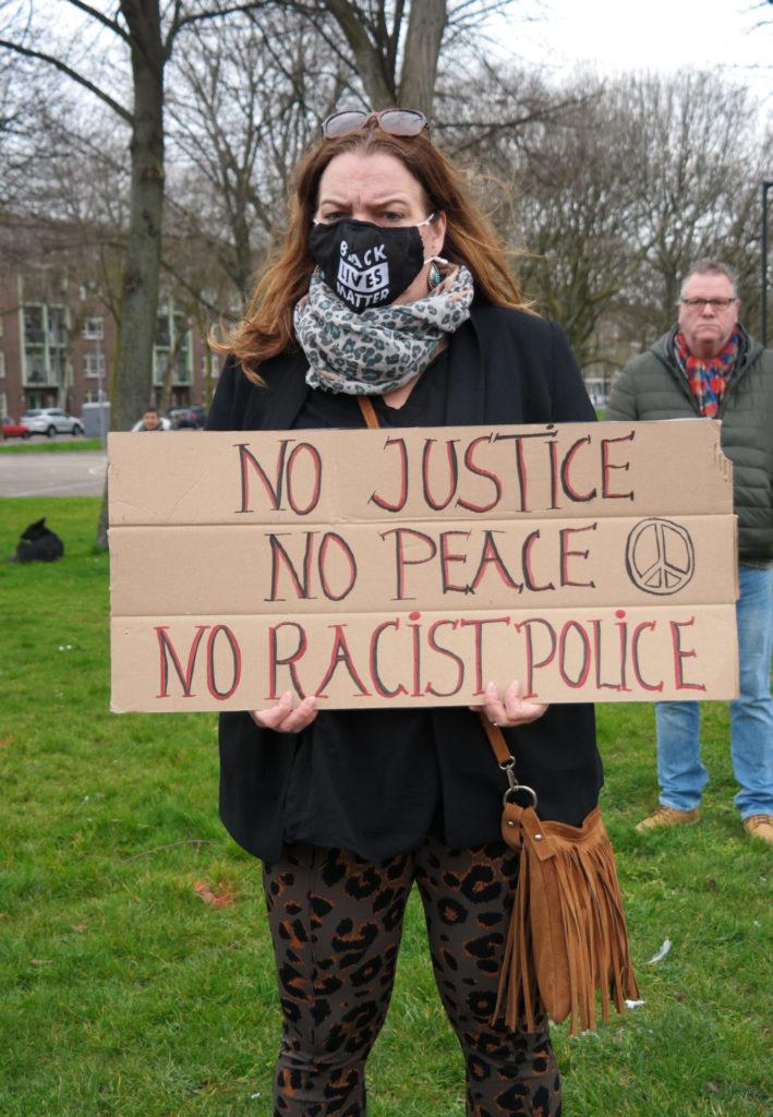 """Een ernstig kijkend persoon met lang rossig haar draagt een bord met de tekst """"No justice, no peace, no racist police"""" en een vredesteken."""