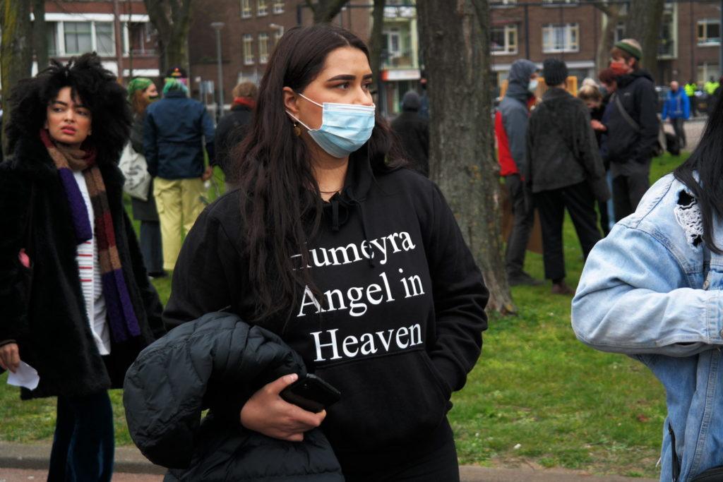 """Een persoon met lange zwarte haren en een blauw wegwerpmondkapje op kijkt naar rechts. Ze draagt een zwarte trui met de tekst """"Humeyra Angel in Heaven""""."""