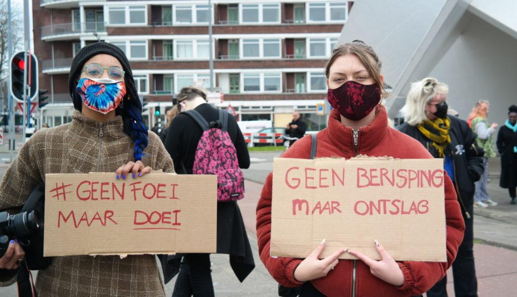 """Twee personen met fleurige mondkapjes en borden met de teksten:  """"#GeenFoeiMaarDoei""""   en  """"Geen berisping maar ontslag""""."""