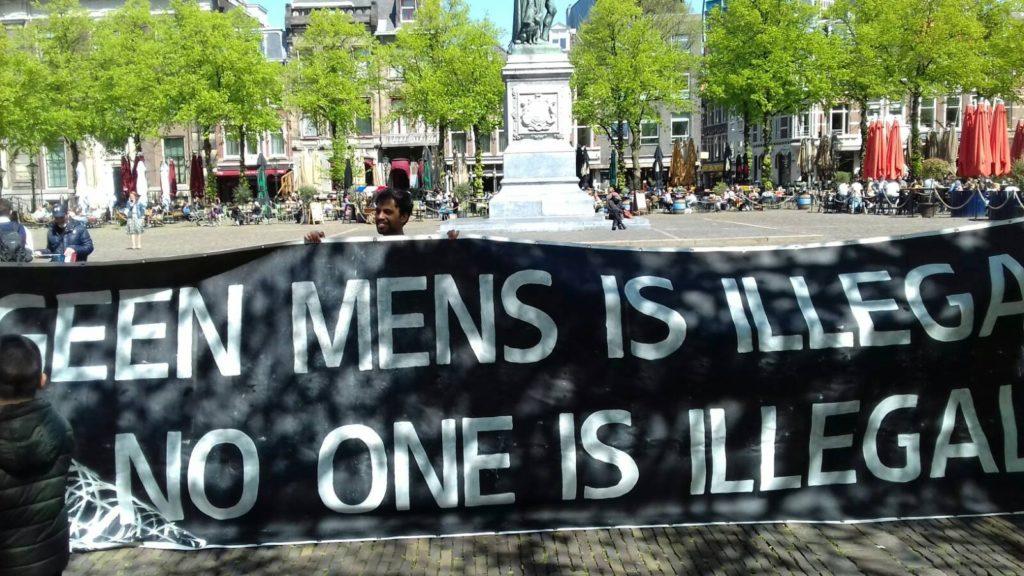 """Enorm spandoek op een zonnig plein, de tekst luidt: """"Geen mens is illegaal / No one is illegal""""."""