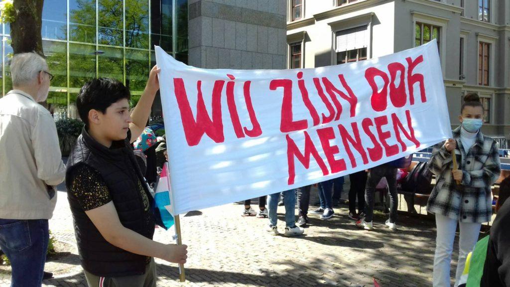"""Twee jonge demonstranten met een spandoek met de tekst: """"Wij zijn ook mensen""""."""